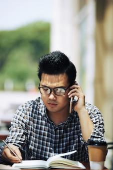Asiatischer mann, der café im im freien sitzt, am handy spricht und in notizbuch schreibt