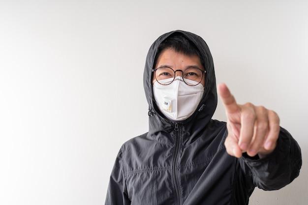 Asiatischer mann, der chirurgische maske trägt, um grippekrankheit koronavirus und staub pm 2,5 zu verhindern