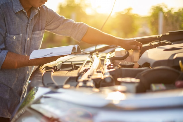 Asiatischer mann, der das autobenutzerhandbuch zur prüfung des motors des modernen autos hält und liest