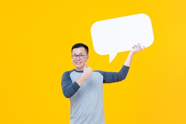 Asiatischer mann, der daumen bis zur leeren spracheblase gibt