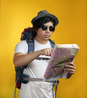 Asiatischer mann, der den großen rucksack zeigt eine karte gegen gelben hintergrund trägt
