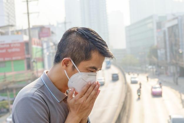 Asiatischer mann, der die atemschutzmaske n95 gegen luftverschmutzung an der straße und am verkehr in bangkok trägt