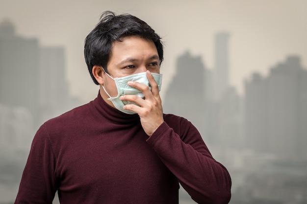 Asiatischer mann, der die gesichtsmaske gegen luftverschmutzung am balkon der hohen wohnung trägt