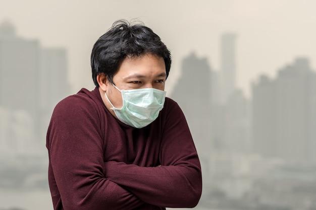Asiatischer mann, der die gesichtsmaske gegen luftverschmutzung mit kälte am balkon trägt