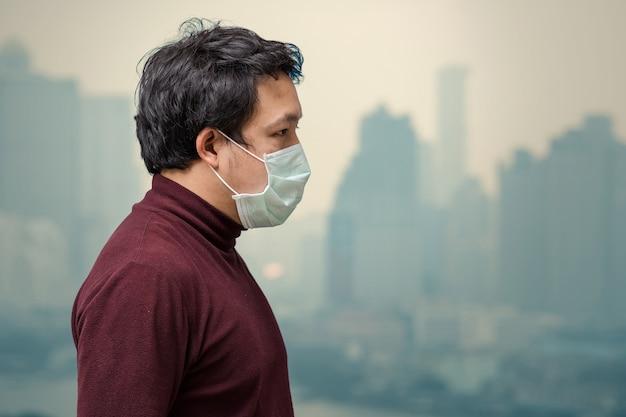 Asiatischer mann, der die gesichtsmaske gegen luftverschmutzung trägt