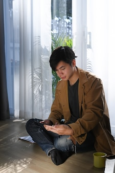 Asiatischer mann, der digitales tablett verwendet und auf holzboden zu hause sitzt.