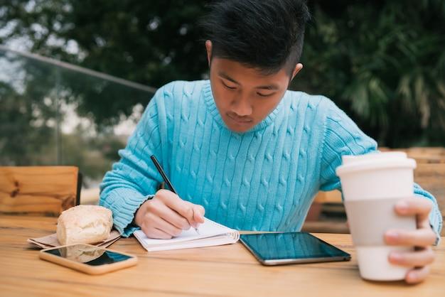 Asiatischer mann, der digitales tablett verwendet und notizen macht