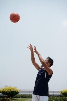 Asiatischer mann, der draußen am stadion steht und baseball oben in einer luft wirft