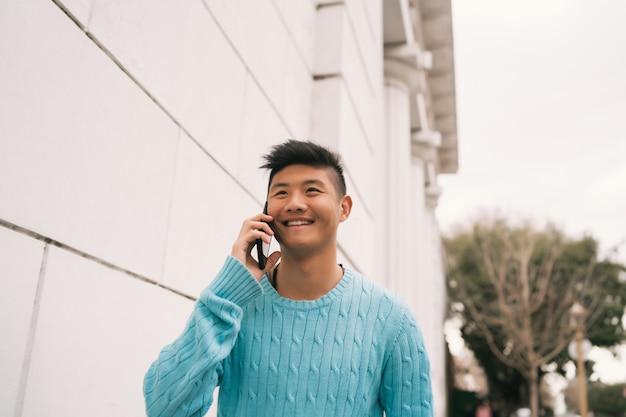 Asiatischer mann, der draußen am telefon spricht