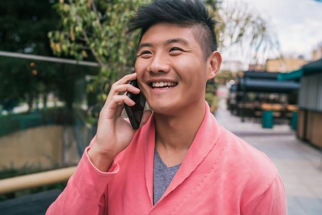 Asiatischer mann, der draußen am telefon spricht.