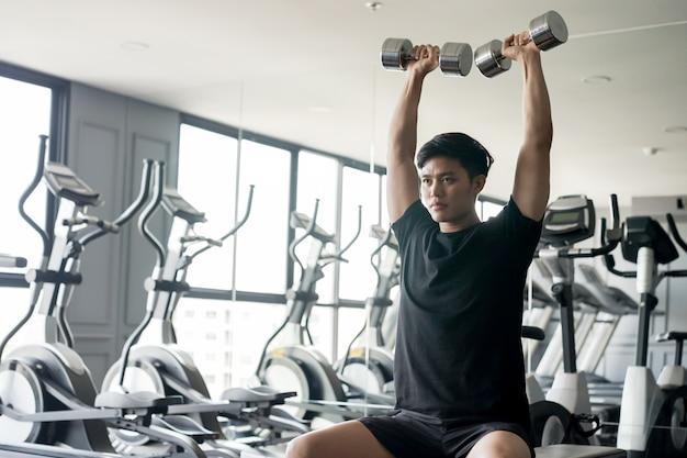 Asiatischer mann, der dummkopf hält und für das spielen der schulterpresse zum gewinnen des muskels an der turnhalle anhebt