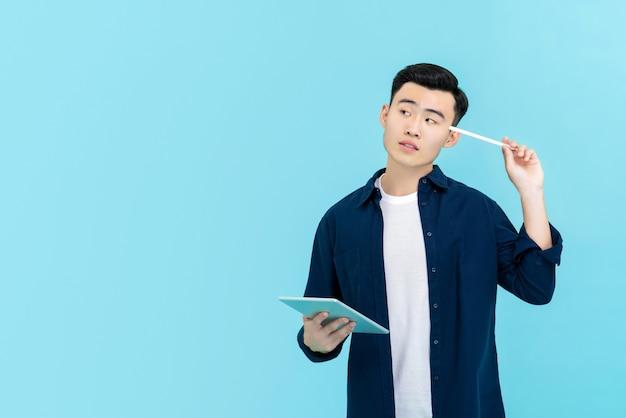 Asiatischer mann, der durchdacht schaut und stift hält, um mit tablette in der hand voranzugehen
