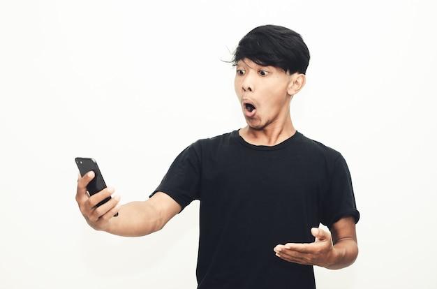 Asiatischer mann, der ein lässiges schwarzes t-shirt mit einem schockierten gesichtsausdruck trägt, als er sein telefon sieht