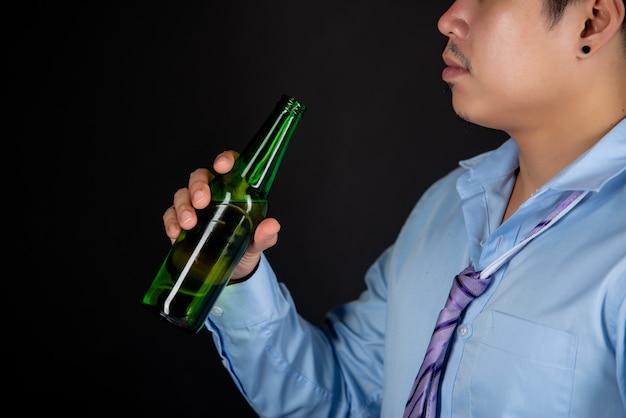 Asiatischer mann, der eine bierflasche trinkt