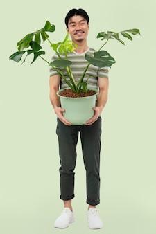 Asiatischer mann, der eine eingetopfte monstera-pflanze hält