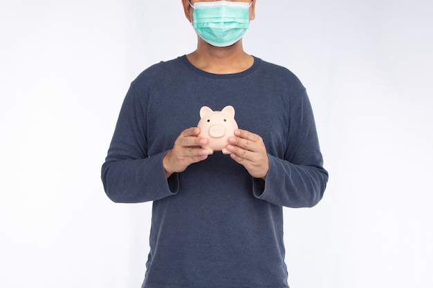Asiatischer mann, der eine gesichtsmaske hält, die rosa sparschwein hält, lokalisiert auf einem weißen hintergrund