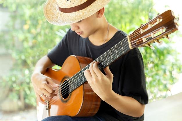 Asiatischer mann, der eine klassische gitarre in der natur spielt.