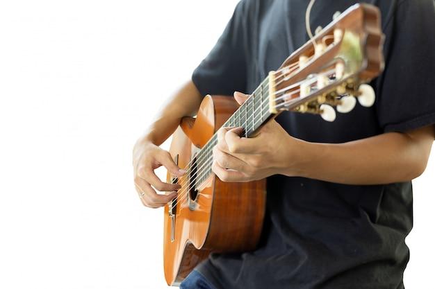 Asiatischer mann, der eine klassische gitarre lokalisiert auf schwarzem hintergrund spielt.
