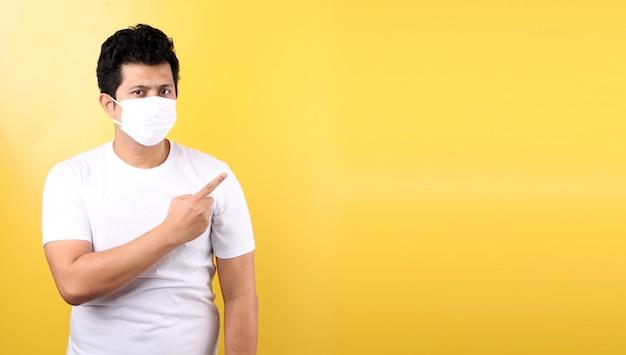 Asiatischer mann, der eine maske trägt, ist krank zeigefinger isoliert