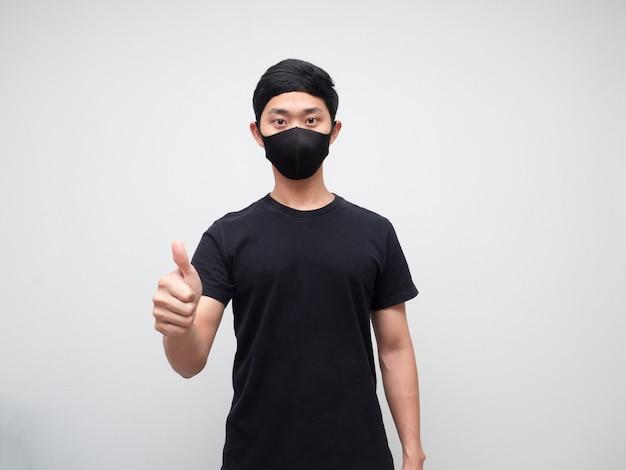 Asiatischer mann, der eine schutzmaske trägt, zeigt den daumen nach oben und schaut auf den weißen hintergrund der kamera