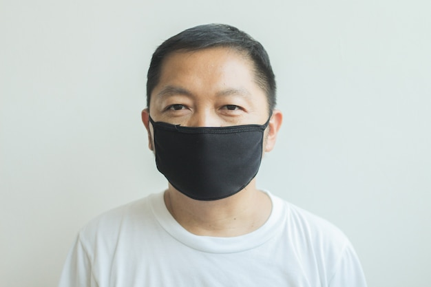 Asiatischer mann, der eine schwarze medizinische maske trägt