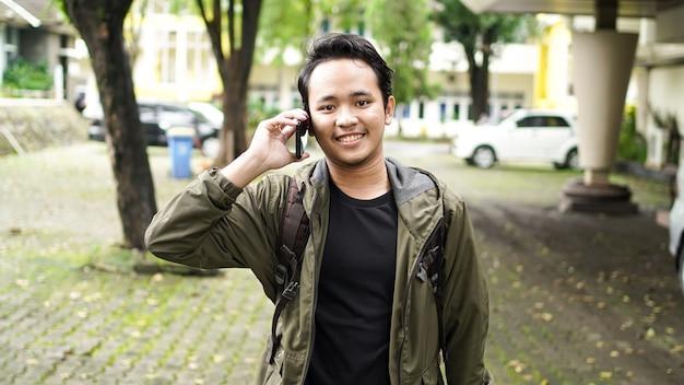 Asiatischer mann, der eine tasche beim telefon trägt