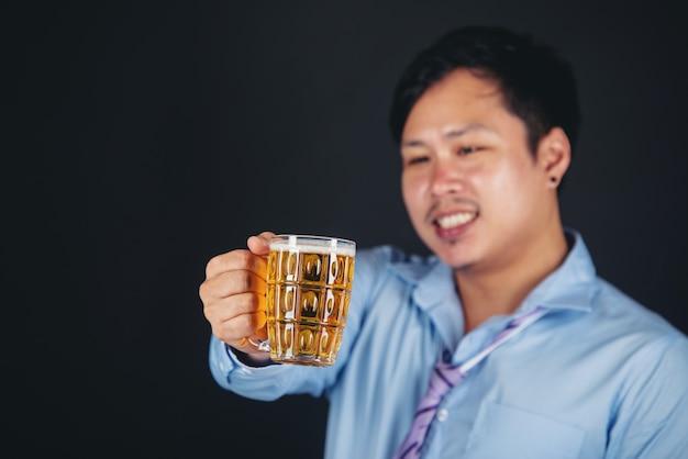 Asiatischer mann, der einen bierkrug trinkt