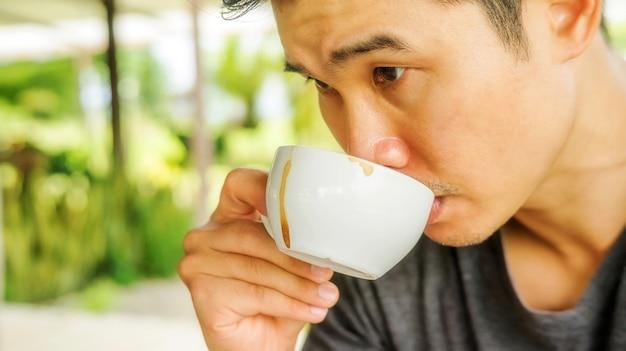 Asiatischer mann, der einen heißen kaffee trinkt