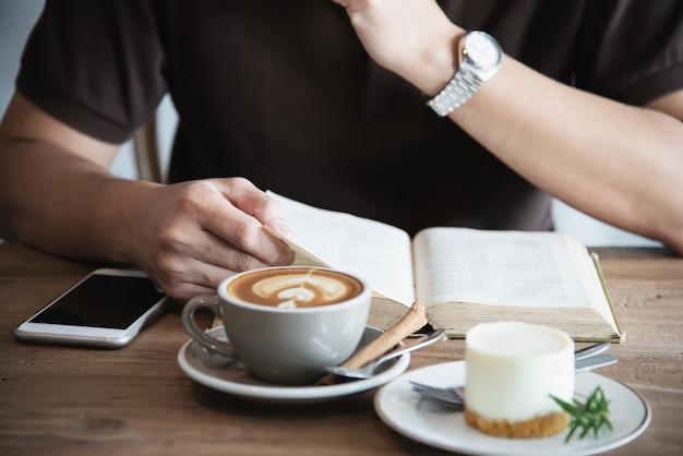 Asiatischer mann, der einen kaffee trinkt und ein buch liest