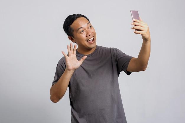 Asiatischer mann, der einen videoanruf mit jemandem über ein smartphone hat