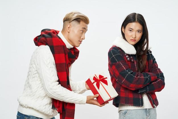 Asiatischer mann, der einer frau ein geschenk gibt, aber sie lehnt es ab. unerwidertes liebeskonzept