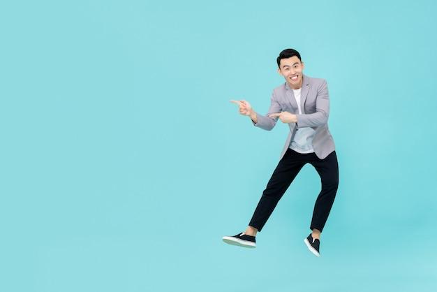 Asiatischer mann, der finger springt und zeigt