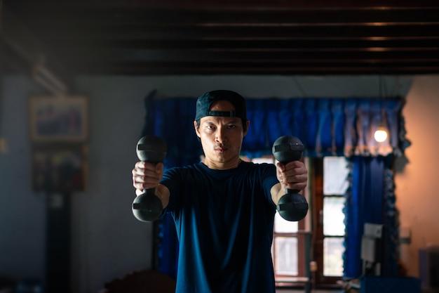 Asiatischer mann, der fitnessübungen mit gewichtheben zu hause tut