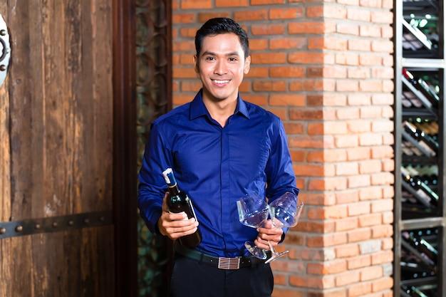 Asiatischer mann, der flasche wein hält