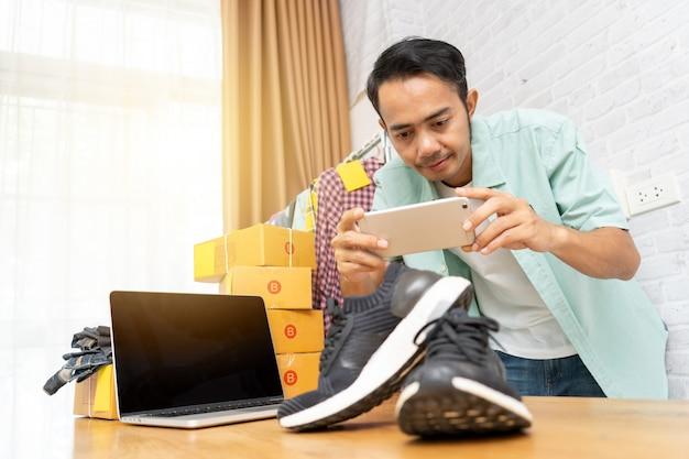 Asiatischer mann, der foto zu den schuhen mit intelligentem telefon machend arbeitet
