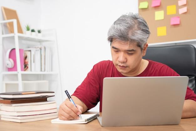 Asiatischer mann, der für neue fähigkeiten vom internet zu hause studiert