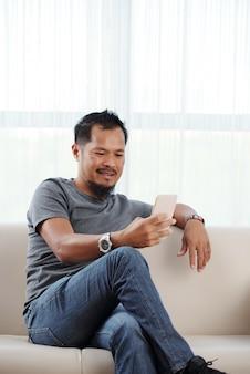 Asiatischer mann, der gemächlich auf couch mit den gekreuzten beinen sitzt und smartphone verwendet