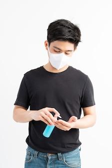 Asiatischer mann, der gesichtsmaske hält, die alkohol zum händewaschen hält, um coronavirus covid-19 im quarantäneraum zu schützen