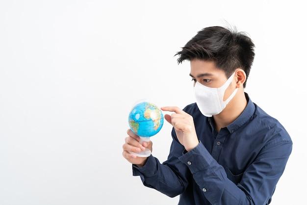 Asiatischer mann, der gesichtsmaske hält karte der globus-weltkarte in der hand hält