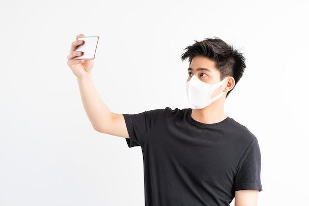 Asiatischer mann, der gesichtsmaske trägt, um coronavirus covid-19 unter verwendung des smartphones im quarantäneraum zu schützen