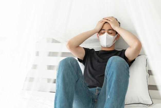 Asiatischer mann, der gesichtsmaske trägt, um krankes kopfschmerz und husten wegen coronavirus covid-19 im quarantäneraum zu schützen