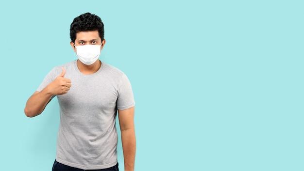 Asiatischer mann, der gesichtsmaske trägt, um vor keim und virus zu schützen, die daumen lokalisiert auf hellblauem hintergrund im studio geben