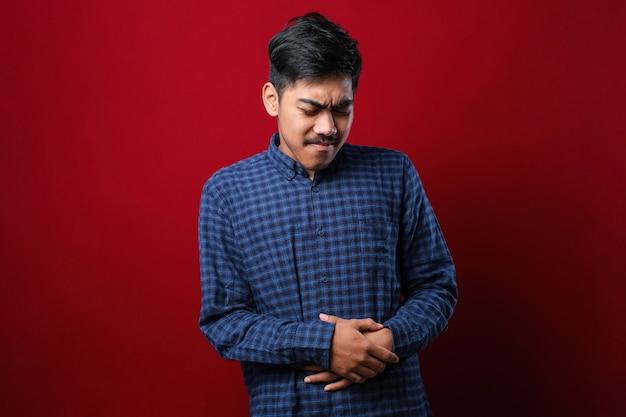 Asiatischer mann, der gesundheitliche probleme mit lässigem hemd durchfallt