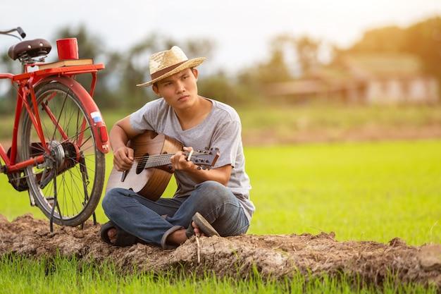 Asiatischer mann, der gitarre am grünen reisfeld in der sonnenuntergangzeit spielt