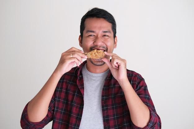 Asiatischer mann, der glücklich lächelt, während er gebratene hähnchenkeule isst