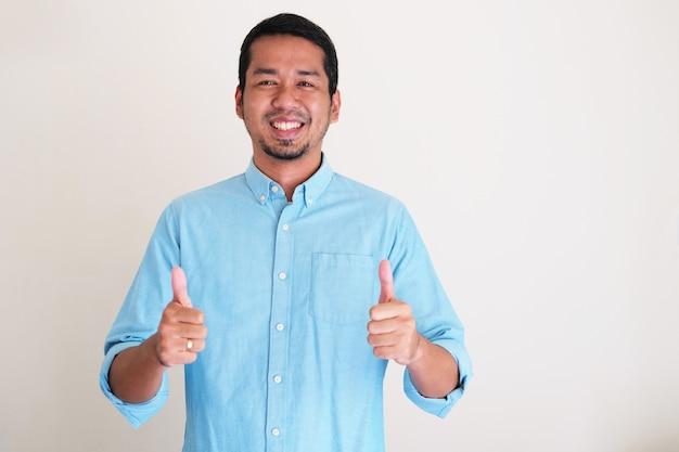Asiatischer mann, der glücklich lächelt, während er zwei daumen hochgibt