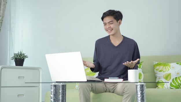 Asiatischer mann, der glücklich von zu hause mit laptop arbeitet