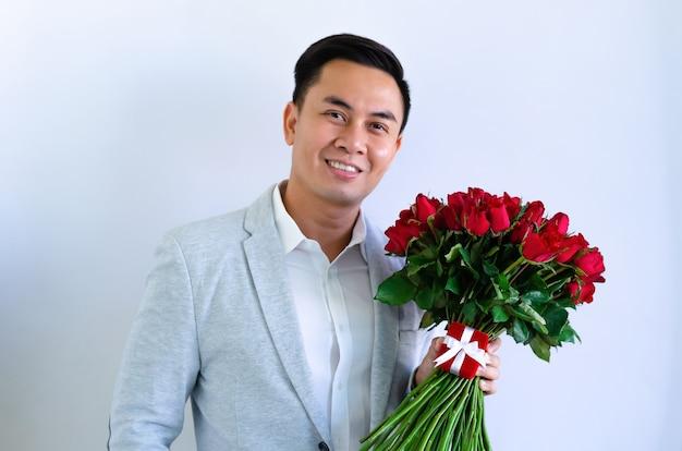 Asiatischer mann, der grauen anzug trägt, der einen blumenstrauß der roten rosen und des roten geschenkkastens lokalisiert im weißen hintergrund für jubiläums- oder valentinstagkonzept hält.