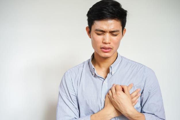 Asiatischer mann, der handmassage auf kasten verwendet, nachdem schmerz, herzinfarkt geglaubt worden ist