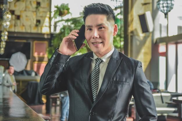 Asiatischer mann, der handy, geschäftsmann ruft handy an